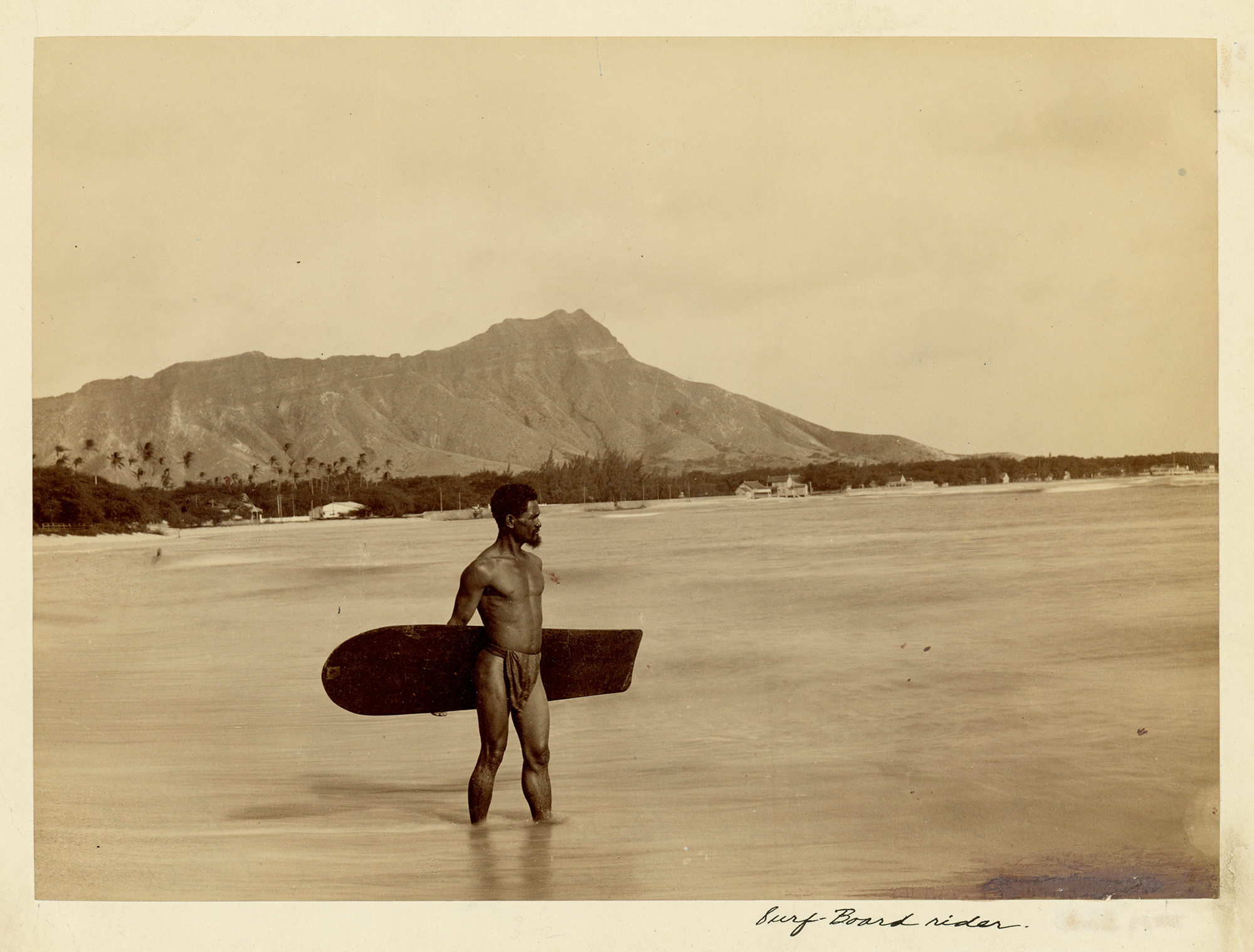 [Hawaiian man with surfboard] Diamond Head in background; Waikīkī, ca. 1890. Photographer unknown.