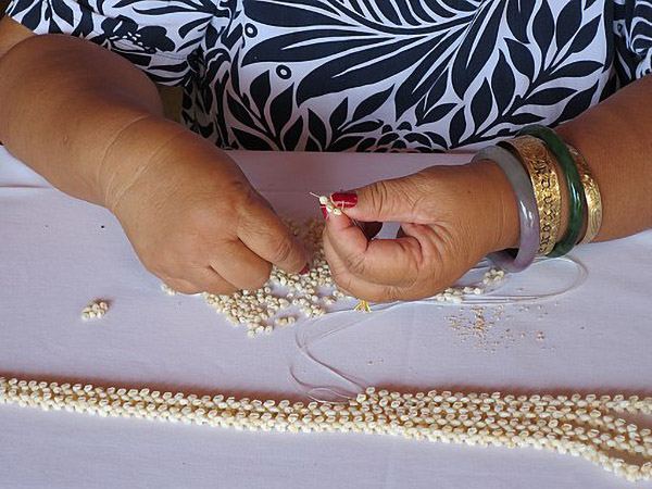 [Niʻihau woman making shell lei] Photo by Hiart.